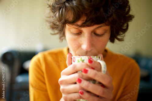 Close up woman sitting at home drinking cup of tea