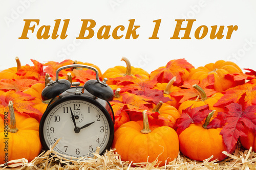 Fotobehang Londen Fall Back 1 hour time change message with a retro alarm clock with pumpkins and fall leaves