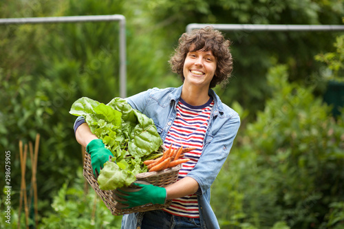 Leinwand Poster female farmer smiling with bunch of vegetables in basket