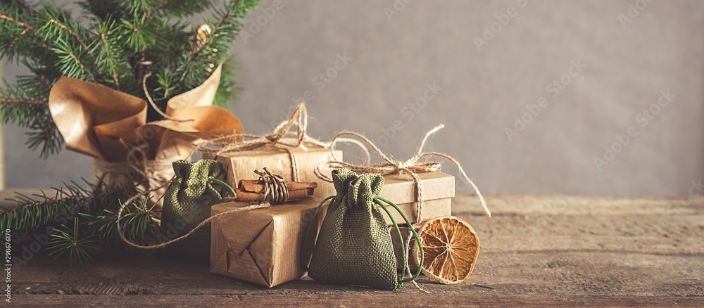 Fototapety, obrazy: Christmas and zero waste, eco friendly packaging. Woman is wrapping gifts in craft paper on a wooden table, ecological Christmas holiday concept, eco decor