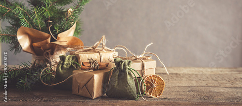Fototapeta Christmas and zero waste, eco friendly packaging. Woman is wrapping gifts in craft paper on a wooden table, ecological Christmas holiday concept, eco decor obraz