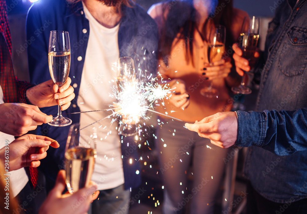 Fototapeta Group of happy people holding sparklers at party and smiling. Young people celebrating New Year together. Friends lit sparklers. Friends enjoying with sparklers in evening. Blur Background.