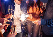 canvas print picture - Group of happy people holding sparklers at party and smiling. Young people celebrating New Year together. Friends lit sparklers. Friends enjoying with sparklers in evening. Blur Background.
