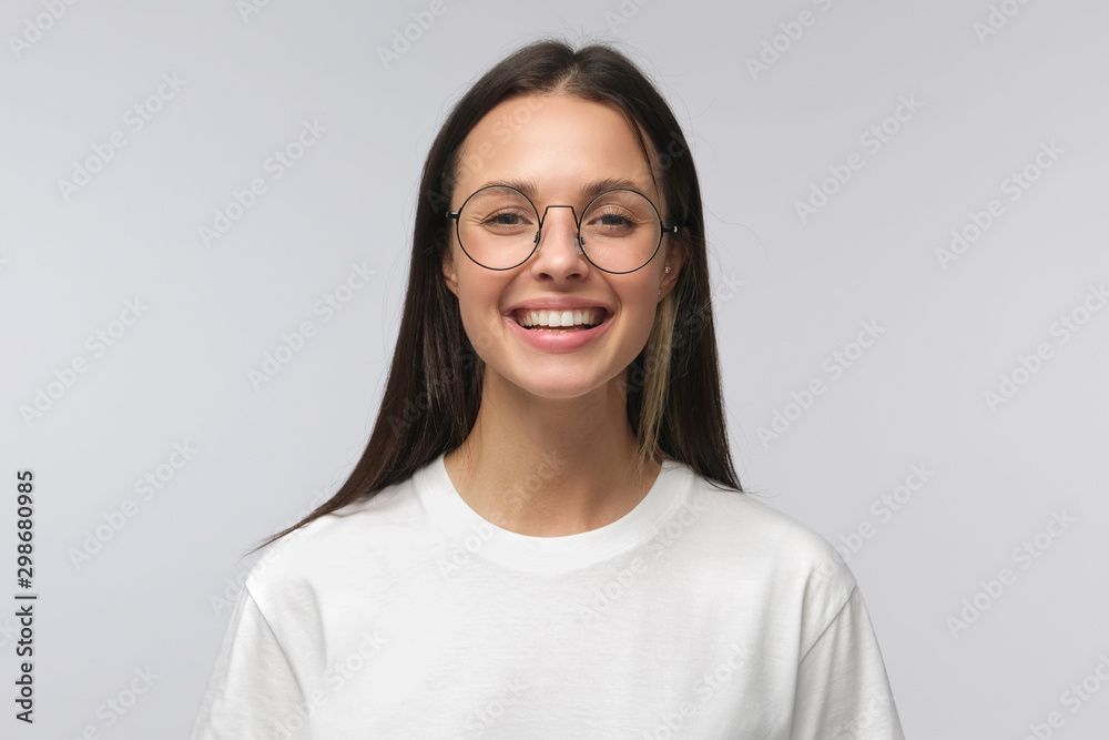 Fototapety, obrazy: European girl wearing big round glasses smiling happily at camera, isolated on gray background