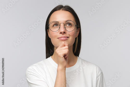 Fototapeta Closeup of young woman dressed in white T-shirt, wearing spectacles and dreaming about something pleasant, isolated obraz na płótnie