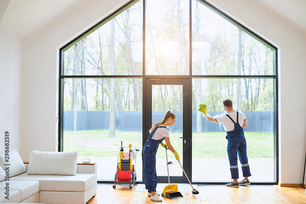 Fototapety, obrazy: Young cleaners in blue uniform mopping wooden floor, cleaning big panoramic window, preparing country house for selling. Cleaning service concept