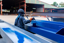 The Painter Is Working To Painting The Steel Structure With Spray Gun At Industrial Factory. Focus On Hand
