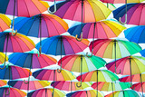 Fototapeta Tęcza - a collection of open umbrellas floating in the air, each umbrella is painted in all colors of the rainbow, photographed from below