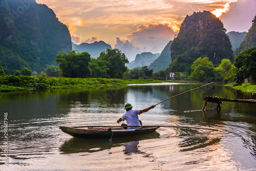 Fisherman on boat in Trang An, near Ninh Binh, Vietnam Wallpaper Mural