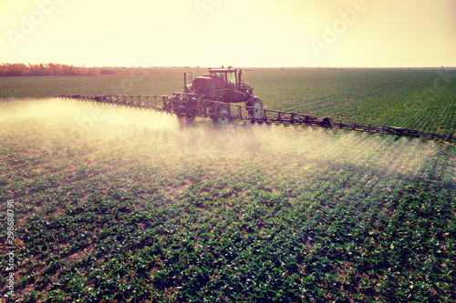 Spoed Fotobehang Weide, Moeras Tractor spraying fertilizer or pesticides on field with sprayer
