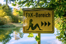German Sign Board Leading The Way To The Nude Swimming Area At The Beach Of Lake Bibi In Bavaria