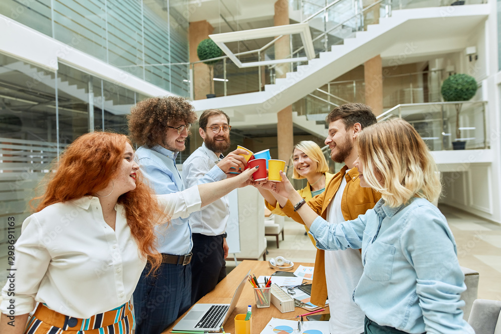 Fototapety, obrazy: Cheerful positive team of young guys stands around table, clink paper glasses in modern designers agency, joyfully looks at each others with satisfied expression, spare time concept