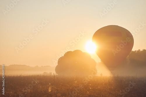A balloon soared into the sky in fog at dawn. Fototapeta