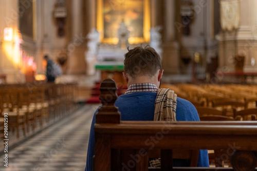 Homme priant dans une église Fototapeta