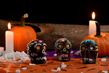 Skulls Made By Hand, Melted Chocolate And Colored Glass. In The Background Some Pumpkins, Candles And Wood. Days Of The Dead Mexican Tradition