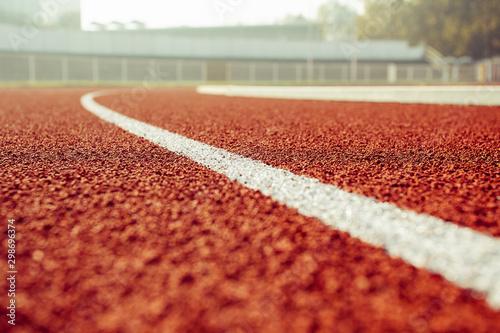 Fotografia Empty red running track in stadium closeup