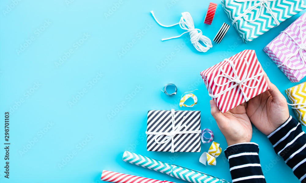 Fototapety, obrazy: Celebration anniversary and party concepts ideas with young female hand wrapping colorful gift box present on blue color