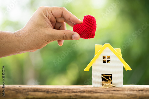 Fotografía  Man hand hold a red heart and home model and gold coin in the middle put on the wood in the public park, saving money for buy house give to the family in the future concept