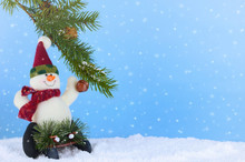 Winter Christmas Scene Of Cute Plush Snowman Playing On Sled Underneath A Pine Branch In Artificial Snow. The Background Is Blue. The Snowman Is Wearing A Fuzzy Winter Hat And Scarf. Digital Snow