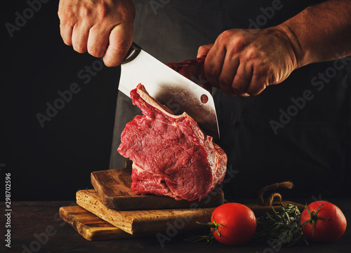 Male butcher cuts raw beef meat. Fototapete