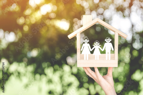 Fotografía  Woman hand holding a wooden home with happy family of paper art is placed inside on nature bokeh in the public park, The saving money for house or real estate owner in the future concept