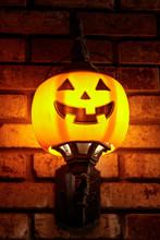 Halloween Pumpkin Light Fixture Decorating A Brick Wall. Bright Jack O Lantern Glowing In The Dark.