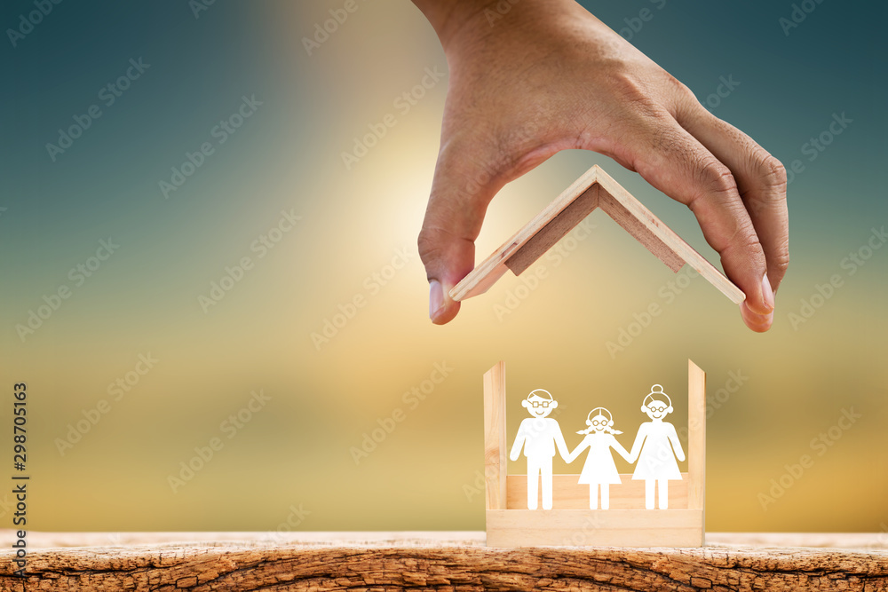 Fototapety, obrazy: Mah hand hold to open a roof and wooden home with happy family of paper art is placed inside on nature sunlight, The saving money for house or business real estate owner in the future concept.