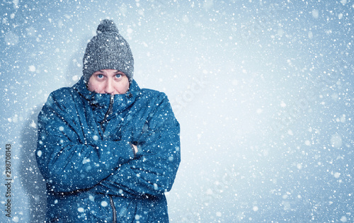 Fotografie, Obraz Frozen man in a blue jacket and hat stands against the wall, snow is falling aro