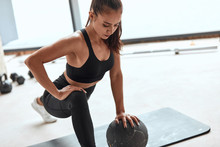 Fit Caucasian Girl In Sportswear Do Push Up With Ball. White Gym Background