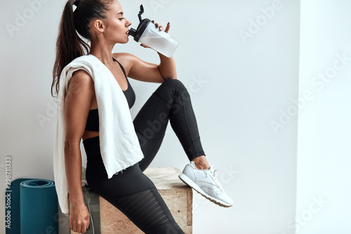 Pinturas sobre lienzo  Attractive slim female drinking water and having rest after fitness, pilates