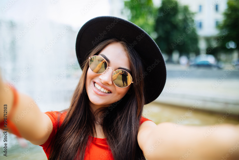 Fototapeta Young woman in hat and sunglasses taking selfie photo near fountain outdoors