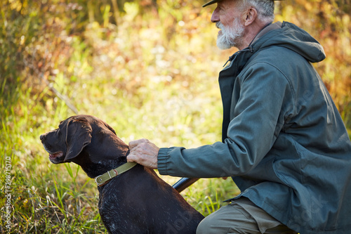 Senior hunter with gun and dog hunting in forest