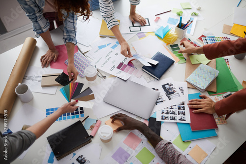 High angle closeup of creative business team working on design project focus on table with photographs and color swatches scattered around, copy space