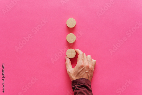 Placing three blank wooden cut circles on pink background