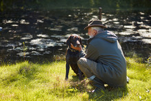 Beautiful Dog Look With Love And Faith On His Owner Hunter. Lake Background