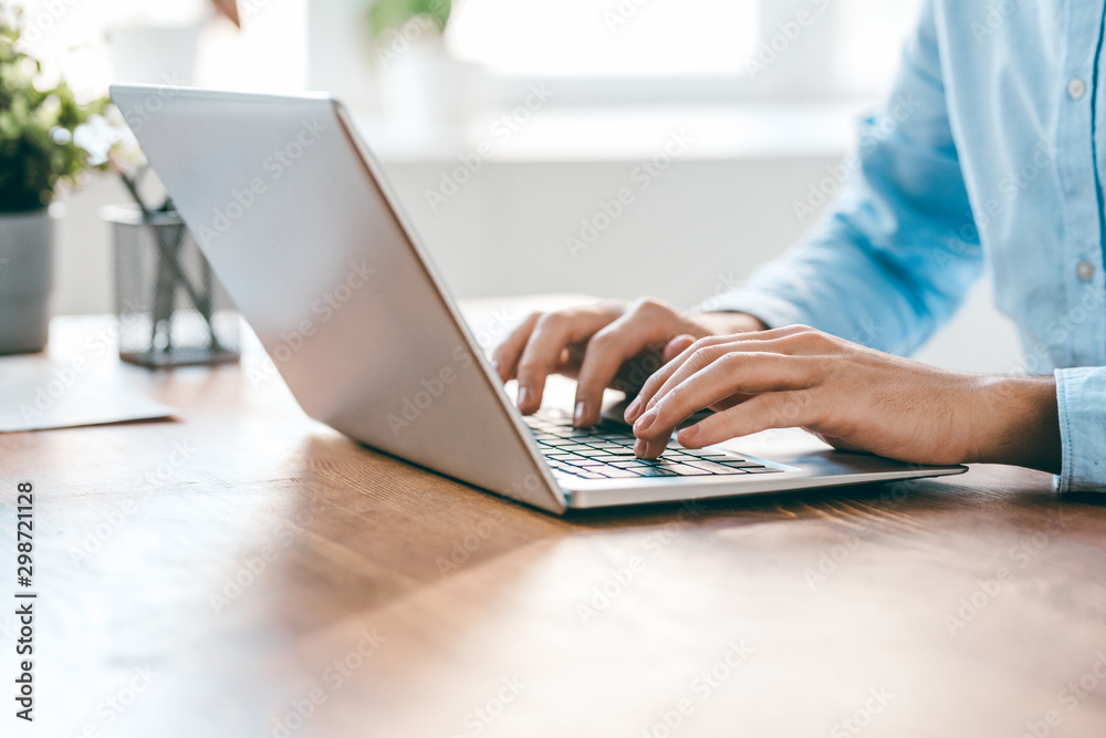 Fototapeta Hands of young contemporary office manager over laptop keypad during work