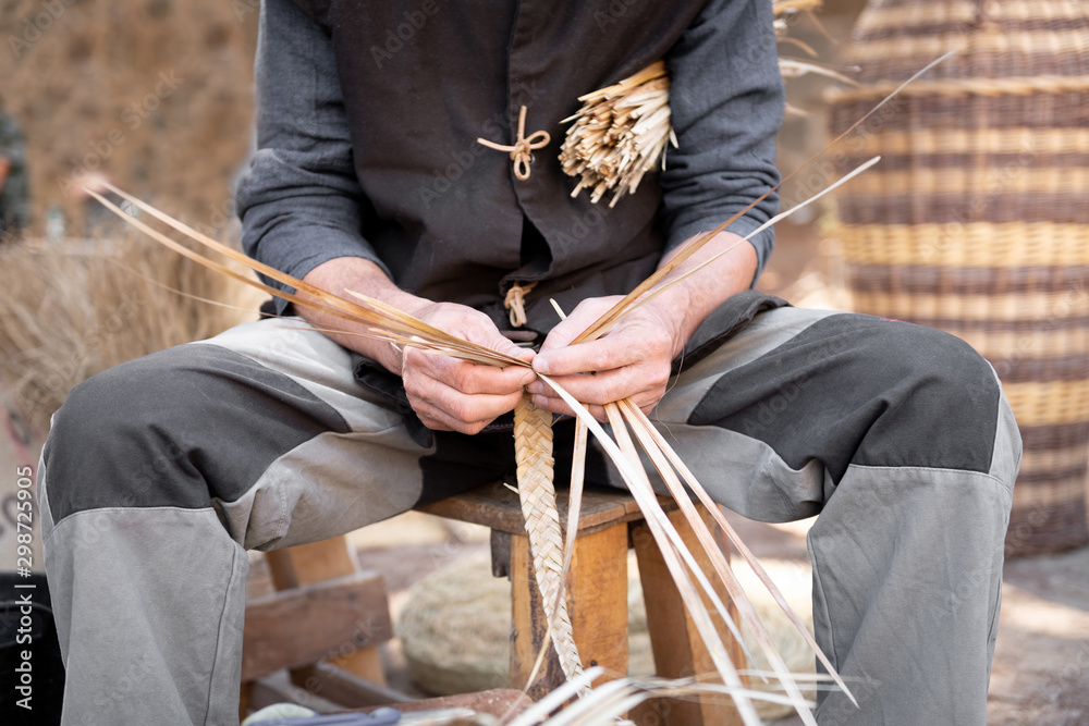 Fototapety, obrazy: old wicker craftsman with hands working in isolated foreground.