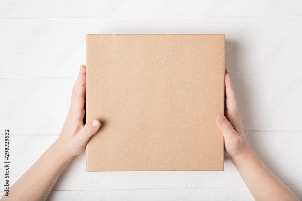 Fototapety, obrazy: Square cardboard box in children hands. Top view, white background