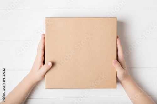 Obraz Square cardboard box in children hands. Top view, white background - fototapety do salonu