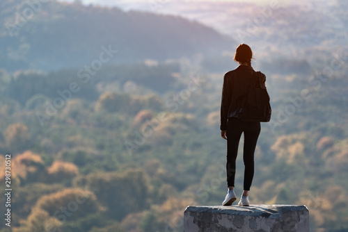 Girl stands on a hill and looks into the distance of the forest. Back view