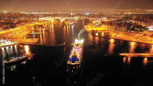 Obraz Aerial drone night shot of beautiful illuminated port of Piraeus and huge cruise liner departing to Aegean popular destinations, Attica, Greece - fototapety do salonu