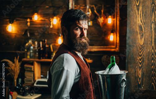 Fényképezés  Handsome bearded barman with long beard and mustache has stylish hair on serious face