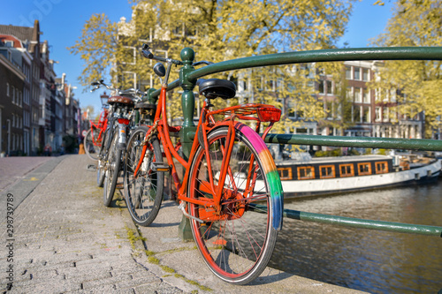 Orange bike with LGBT flag parked on a bridge in Amsterdam, Netherlands