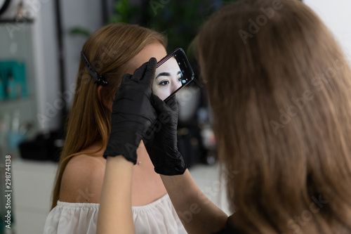 Young beautician caucasian girl holds model eyebrow correction Fototapet