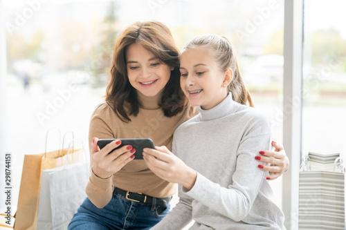 Joyful young mother and her daughter using video-chat in smartphone Billede på lærred