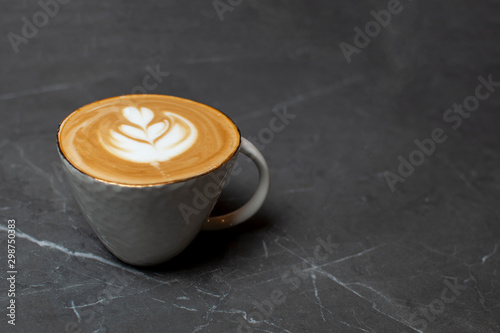 Canvas Prints Cafe one cup of coffee stands on a granite table, latte art on foam