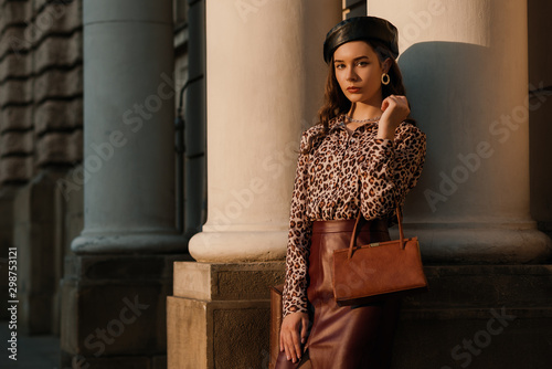 Obraz Outdoor fashion portrait of young elegant luxury woman wearing leopard print shirt, faux leather skirt, beret, holding small brown classic bag, handbag, posing in street Copy, empty space for text  - fototapety do salonu