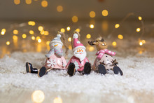 Decorative Figurines Of A Christmas Theme. Set Of Statuettes Of Santa, Snowman And Deer. Christmas Tree Decoration. Festive Decor, Warm Bokeh Lights.