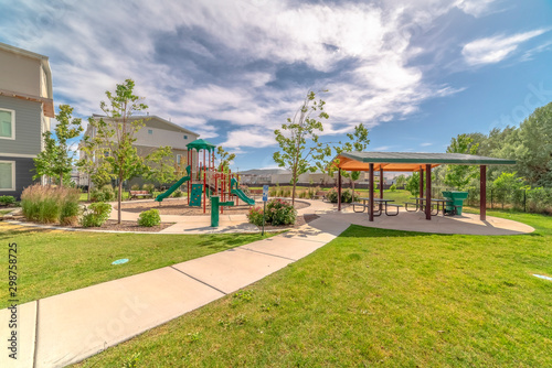 Park at a sunny neighborhood with childrens playground and pavilion eating area Wallpaper Mural