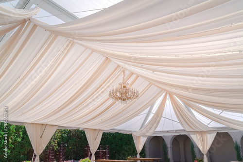 Valokuva  Stunning wedding venue with white canopy and curtains under the glass roof